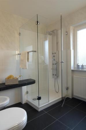 Dusche mit Duschpanell und angeformter Sitzbank in schwarz.