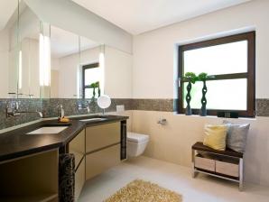Handtücher und Kissen von Leitner und der goldene Badeteppich runden das Bild harmonisch ab.