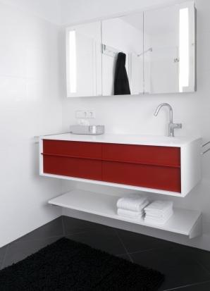 Die weiße Ablage unter dem Waschtisch ist eine weitere Abstellmöglichkeit für Duschtücher und Körbe.