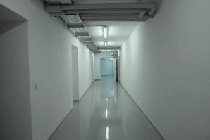 Flur mit staplerfestem Boden, Elektrotrasse, Heizungsleitungen und Brandschutztüren.