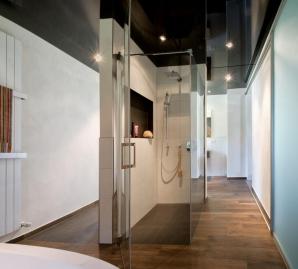 Das Badezimmer besticht dank einer spiegelnden Lackspanndecke durch zeitlose Eleganz.