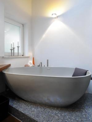 Ovale freistehende Wanne aus Mitek schmiegt sich an die Badwand.
