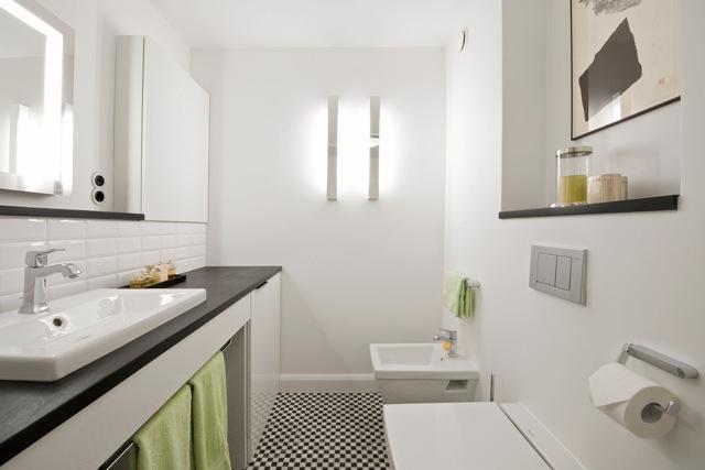 Aufgrund des schlichten Gestaltungskonzepts in Schwarz und Weiß passen auch andere Farben wie Grün wunderbar in das Bad.