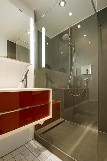 Das Grau der großformatigen Fliesen strahlt Ruhe aus, während das Rot im Waschbereich frische Akzente setzt.