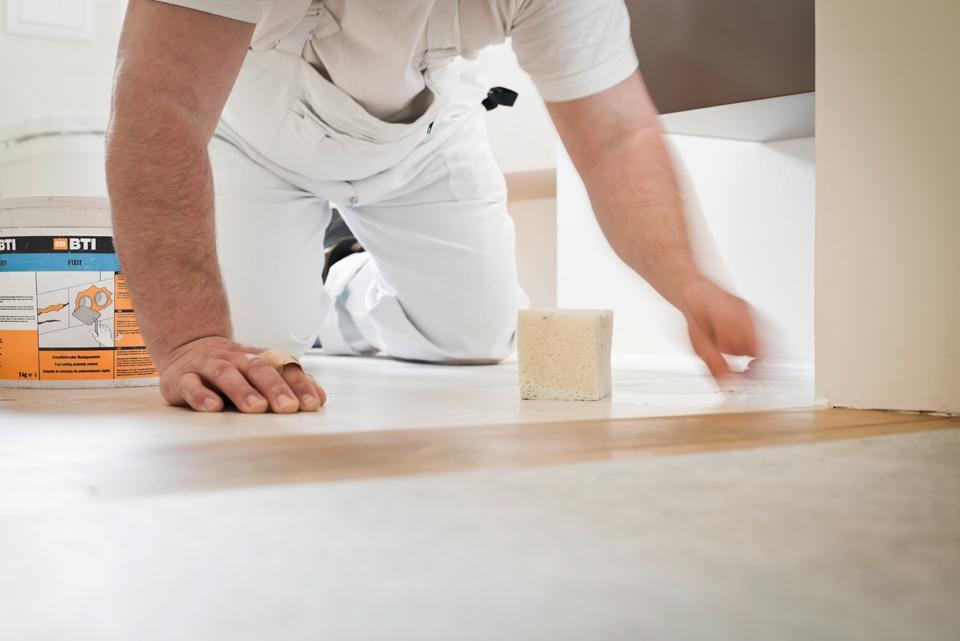 Bild eines Monteures bei der Bearbeitung eines Badbodens